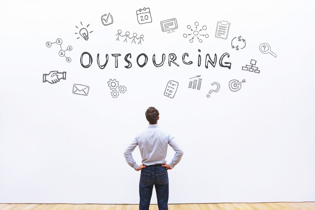 outsourcing concept - a man standing in front of some icons and an Outsourcing headline