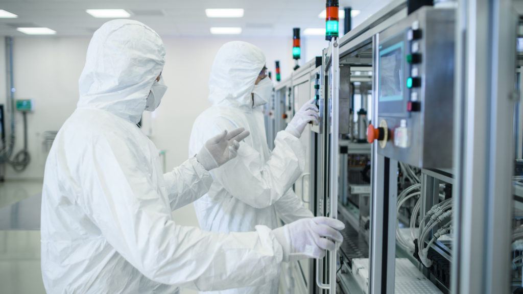 Team of Scientists in Sterile Protective Clothing Work on a Modern Industrial 3D Printing Machinery. Pharmaceutical, Biotechnological and Semiconductor Creating / Manufacturing Process.